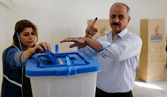 An Iraqi Kurdish man holds up his finger marked with ink as he casts his ballot during parliamentary elections in Irbil, Iraq, Sunday, Sept. 30, 2018. Iraq's self-ruled Kurdish region was holding long-delayed parliamentary elections on Sunday, a year after a vote for independence sparked a punishing backlash from Baghdad, leaving Kurdish leaders deeply divided. (AP Photo)