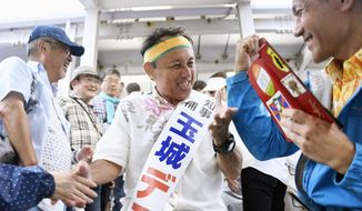 In this Sept. 28, 2018, photo, Denny Tamaki, a legislator, center shakes hands with supporters during his election campaign for Okinawa governor in Naha city. Okinawans are choosing a governor in an election Sunday, Sept. 30, that many see hinging on how voters feel about the American military presence on the southwestern Japanese island.(Koji Harada/Kyodo News via AP)
