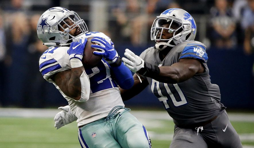 Dallas Cowboys running back Ezekiel Elliott (21) catches a pass in front of Detroit Lions linebacker Jarrad Davis (40) in the second half of an NFL football game in Arlington, Texas, Sunday, Sept. 30, 2018. (AP Photo/Ron Jenkins)