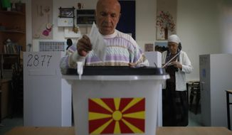 A man casts his ballot in at a polling station during a referendum in Skopje, Macedonia, Sunday, Sept. 30, 2018. Macedonians were deciding Sunday on their country's future, voting in a crucial referendum on whether to accept a landmark deal ending a decades-old dispute with neighbouring Greece by changing their country's name to North Macedonia, to qualify for NATO membership and also pave its way toward the European Union. (AP Photo/Thanassis Stavrakis)