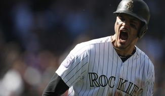 Colorado Rockies' Nolan Arenado yells as he circles the bases after hitting a two-run home run off Washington Nationals starting pitcher Erick Fedde in the first inning of a baseball game Sunday, Sept. 30, 2018, in Denver. The Rockies won 12-0. (AP Photo/David Zalubowski)