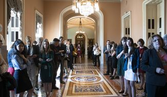 Congressional reporters line the hallway outside the office of Senate Majority Leader Mitch McConnell, R-Ky., as he meets with Senate Judiciary Committee Chairman Chuck Grassley, R-Iowa, and other leaders where they agreed to delay a final vote on Supreme Court nominee Brett Kavanaugh to allow time for an investigation by the FBI of the sexual misconduct allegations against him, at the Capitol in Washington, Friday, Sept. 28, 2018. (AP Photo/J. Scott Applewhite)