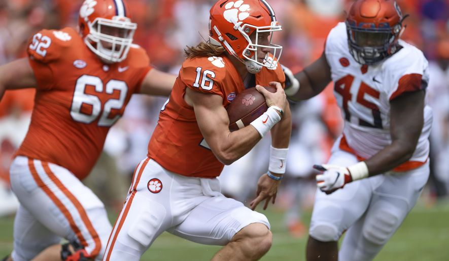 Clemson quarterback Trevor Lawrence scrambles out of the pocket with blocking help from Cade Stewart (62) as Syracuse's Kenneth Ruff chaes during the first half of an NCAA college football game Saturday, Sept. 29, 2018, in Clemson, S.C. Clemson won 27-23. (AP Photo/Richard Shiro)