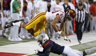 Arizona safety Christian Young upends Southern California tight end Josh Falo (83) in the first half during an NCAA college football game, Saturday, Sept. 29, 2018, in Tucson, Ariz. (AP Photo/Rick Scuteri)