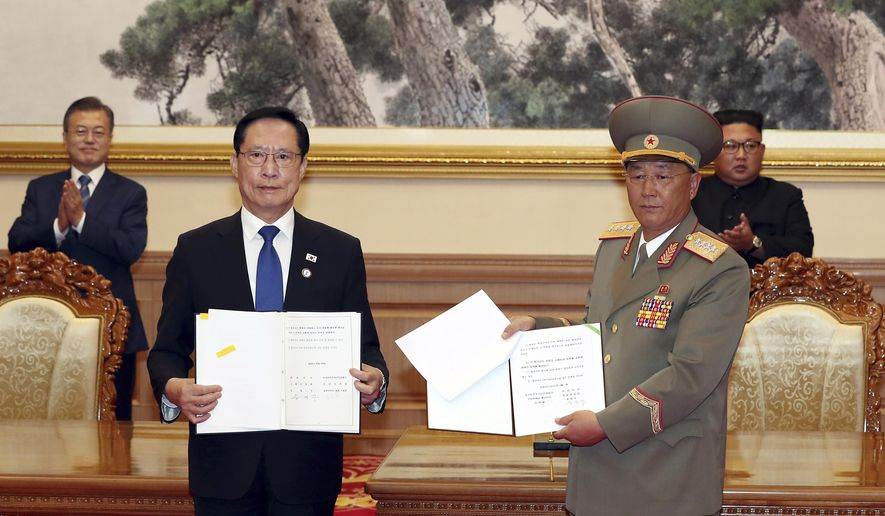 FILE - In this Sept. 19, 2018, file photo, South Korea's Defense Minister Song Young-moo, front left, and North Korea's Minister of the People's Armed Forces No Kwang Chol, front right, hold the documents after signing as South Korean President Moon Jae-in, rear left, and North Korean leader Kim Jong Un, rear right, clap at the Paekhwawon State Guesthouse in Pyongyang, North Korea. North and South Korea began removing mines at two sites inside their heavily fortified border Monday, Oct. 1,  as part of their recent deals to ease decades-long military tensions.(Pyongyang Press Corps Pool via AP, File)