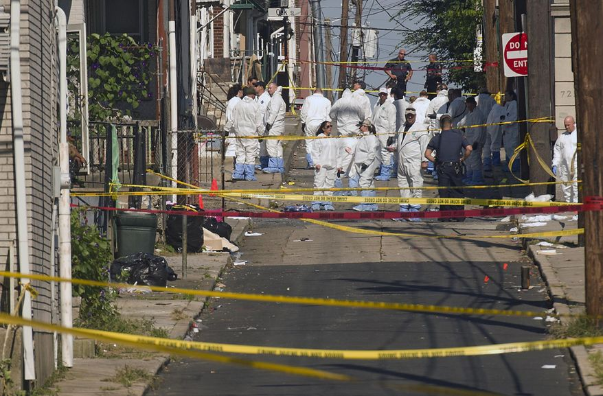 Federal and local authorities investigate along North Hall Street in Allentown, Pa., Sunday, Sept. 30, 2018, after a fiery car explosion rocked the neighborhood on Saturday night. Police confirmed several fatalities. (Harry Fisher/The Morning Call via AP)