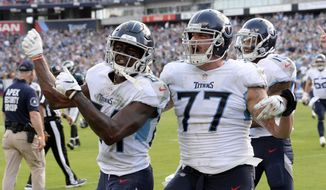 Tennessee Titans wide receiver Corey Davis (84) celebrates with offensive tackle Taylor Lewan (77) after Davis caught the winning touchdown pass against the Philadelphia Eagles in overtime of an NFL football game Sunday, Sept. 30, 2018, in Nashville, Tenn. The Titans won 26-23. (AP Photo/Mark Zaleski)