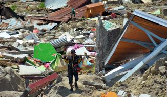 A man carry items he saved from the rubble following a major earthquake and tsunami in Palu, Central Sulawesi, Indonesia, Monday, Oct. 1, 2018. A mass burial of earthquake and tsunami victims was being prepared in a hard-hit city Monday as the need for heavy equipment to dig for survivors of the disaster that struck a central Indonesian island three days ago grows desperate.(AP Photo/Rifki)