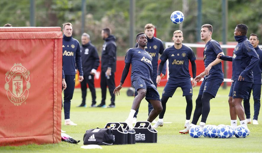 Manchester United's Paul Pogba, center, attends a training session at the AON Training Complex, Carrington, north west England, Monday Oct. 1, 2018. (Martin Rickett/PA via AP)
