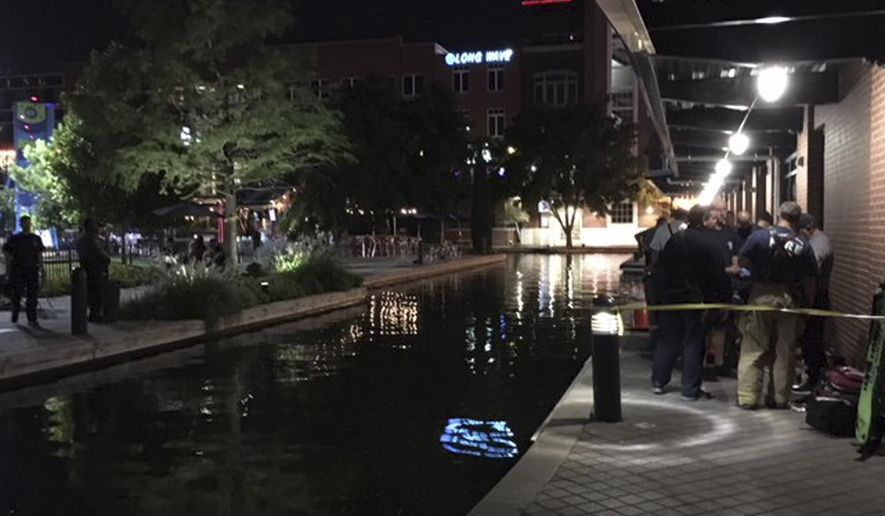 This photo provided by the Oklahoma City Fire Department, shows the scene at the Bricktown canal in Oklahoma City, Sunday, Sept. 30, 2018, where one man died and another is in critical condition after being electrocuted in the canal. (Oklahoma City Fire Department via AP)