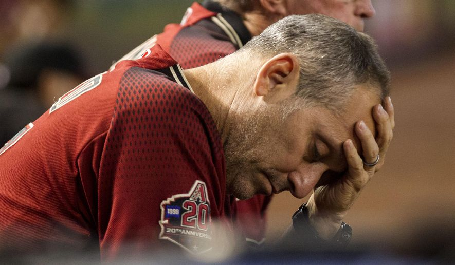 FILE - In this Sept. 23, 2018, file photo, Arizona Diamondbacks manager Torey Lovullo wipes his brow during a baseball game against the Colorado Rockies, in Phoenix. The Diamondbacks were in contention for a second straight playoff appearance late into the season. A late collapse knocked them out of the race and may have put them at a crossroads. (AP Photo/Darryl Webb, File)