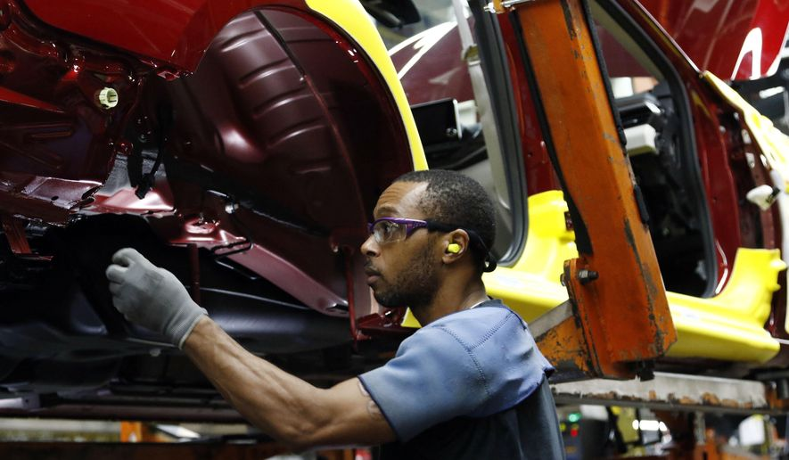 FILE- In this Sept. 27, 2018, file photo a line technician works on assembling a redesigned Nissan Altima sedan at its Nissan Canton Vehicle Assembly Plant in Canton, Miss. On Monday, Oct. 1, the Institute for Supply Management, a trade group of purchasing managers, issues its index of manufacturing activity for September. (AP Photo/Rogelio V. Solis, File)