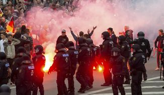 """FILE - In this Aug. 27, 2018 photo protesters light fireworks during a far-right demonstration in Chemnitz, Germany. German prosecutors say they have ordered the arrest of six men on suspicion of forming a """"far-right terrorist organization"""" in the eastern city of Chemnitz, where anti-migrant violence flared this summer. Prosecutors said in a statement the men planned to carry out armed attacks against foreigners and political enemies.   (AP Photo/Jens Meyer, file)"""