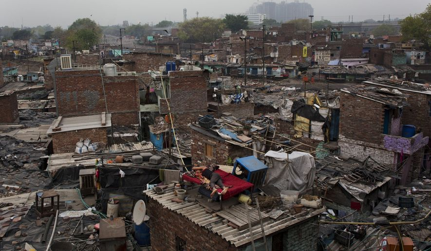 In this April 20, 2015 file photo, an Indian man sleeps on the roof of his house at a shanty area in New Delhi, India. The United Nations is celebrating a government program officials say can be a model for other low-income and developing countries at a summit this week in New Delhi. (AP Photo/Bernat Armangue)