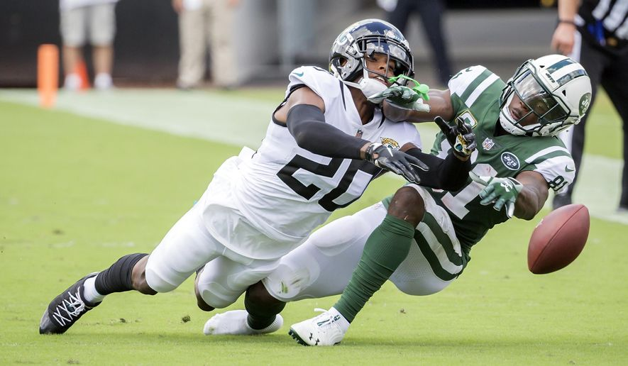 Jacksonville Jaguars cornerback Jalen Ramsey (20) breaks up a pass intended for New York Jets wide receiver Quincy Enunwa, right, during the first half of an NFL football game, Sunday, Sept. 30, 2018, in Jacksonville, Fla. (AP Photo/Stephen B. Morton)