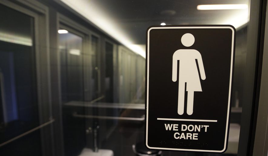 This May 12, 2016, file photo, shows signage outside a restroom at 21c Museum Hotel in Durham, N.C. (AP Photo/Gerry Broome, File)