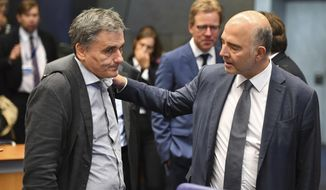 European Commissioner for Economic and Financial Affairs Pierre Moscovici, right, speaks with Greek Finance Minister Euclid Tsakalotos during a round table meeting of eurogroup finance ministers at the European Council building in Luxembourg, Monday, Oct. 1, 2018. (AP Photo/Geert Vanden Wijngaert)