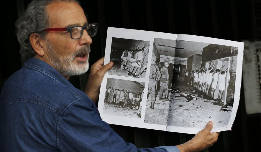 In this Sept. 18, 2018 photo, Enrique Espinosa shows a magazine photo in which he and other demonstrators are being detained by armed soldiers during the Tlatelolco massacre in Mexico City. As Mexico marks 50 years since the killings of student protesters at Tlatelolco plaza, the massacre remains an open wound. (AP Photo/Marco Ugarte)