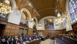 View of the U.N. World Court where judges delivered their verdict on a request by Bolivia, left table, for judges to order Chile, rear center table, to enter talks over granting its landlocked neighbor access to the Pacific Ocean, in The Hague, Netherlands, Monday, Oct. 1, 2018. (AP Photo/Peter Dejong)