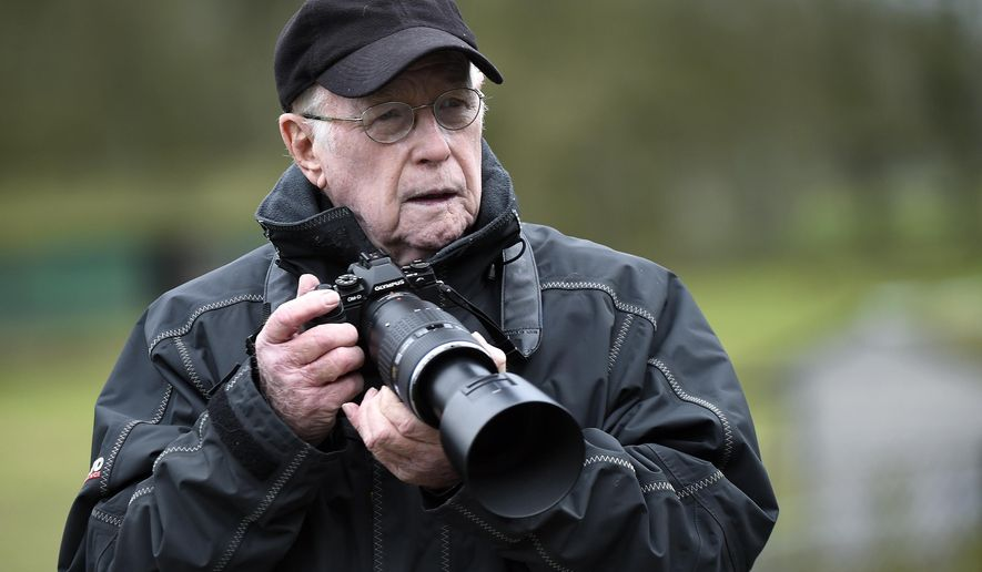 In this February 2016 photo, Max Nash takes photos in Bedfordshire. Nash, who covered the conflicts in Southeast Asia and the Middle East and helped nurture a new generation of female photojournalists during more than 40 years with The Associated Press, died Friday, Sept. 28, 2018, after collapsing at home. He was 77. (Tony Margiocchi via AP)