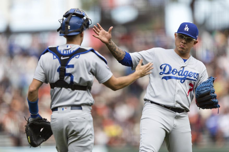 Los Angeles Dodgers catcher Austin Barnes, left, and relief pitcher Julio Urias celebrate defeating the San Francisco Giants in a baseball game in San Francisco, Sunday, Sept. 30, 2018. (AP Photo/John Hefti)