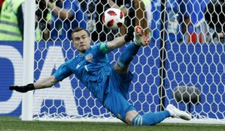 FILE - In this July 1, 2018, file photo Russia goalkeeper Igor Akinfeev catches a penalty shot during the round of 16 match between Spain and Russia at the 2018 soccer World Cup at the Luzhniki Stadium in Moscow, Russia. Akinfeev, whose penalty shootout saves helped the World Cup host nation eliminate Spain, has retired from the national team. (AP Photo/Victor R. Caivano, File)