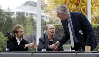 FILE - In this April 11, 2018, file photo, Tod Leiweke, right, greets part owners Jerry Bruckheimer, left, and David Bonderman to start a news conference naming Leiweke as the president and CEO for a prospective NHL expansion team in Seattle. The prospective owners of an NHL expansion team in Seattle will make their pitch to an executive committee of owners in New York on Tuesday, Oct. 2, 2018, with a vote by the full Board of Governors possibly as early as December and almost a virtual certainty the puck drops in Seattle two or three years from now. (AP Photo/Elaine Thompson, File)