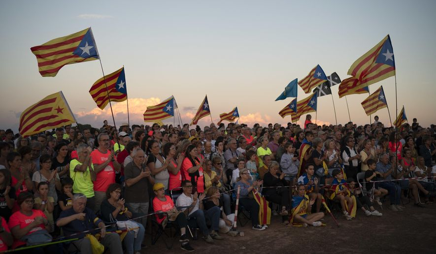 """Pro independence demonstrators wave """"esteladas"""" or independence flags as they gather in a field overlooking the Lledoners prison in Sant Joan de Vilatorrada, about 50 kilometres away from Barcelona, Spain, Sunday, Sept. 30, 2018. Hundreds of Catalonia residents gathered near the Lledoners prison, where most prominent jailed separatists are awaiting trial, to mark nearly one-year since an unauthorized independence referendum was held in this region of Spain last year. (AP Photo/Felipe Dana)"""
