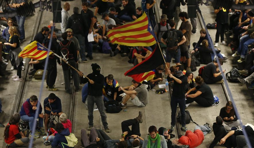 Activists advocating for Catalan secession wave Catalonian independence flags as others sit on the railway tracks at the station in Girona, Spain, Monday Oct. 1, 2018. Activists blocked major highways, train lines and avenues across the northeastern region one year after a banned referendum crushed by police failed to deliver an independent state. (AP Photo/Manu Fernandez)