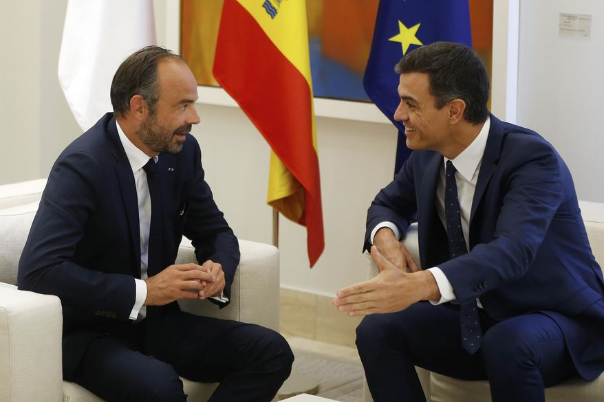 French Prime Minister Edouard Philippe, left, and his Spanish counterpart Pedro Sanchez talk at the start of a meeting on cooperation against terrorism, at the Moncloa Palace in Madrid, Spain, Monday, Oct. 1, 2018. (AP Photo/Paul White)