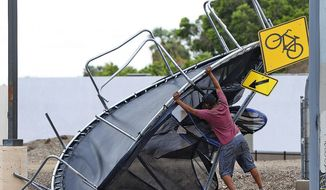 Joel Negrete, 510 S. Avenue A, begins moving a trampoline that was once in his yard before the start of Sunday's early afternoon rain storm. Tropical Storm Rosa neared Mexico's Baja California on Monday, spreading heavy rains that were projected to extend into a drenching of the U.S. Southwest. (Randy Hoeft/Yuma Sun via AP)/The Yuma Sun via AP)