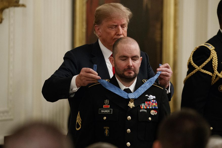 President Donald Trump presents the Congressional Medal of Honor to former Army Staff Sgt. Ronald J. Shurer II for actions in Afghanistan, in the East Room of the White House, Monday, Oct. 1, 2018, in Washington. (AP Photo/Evan Vucci)