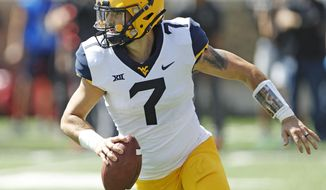 West Virginia's Will Grier (7) looks to pass the ball during the second half of an NCAA college football game against Texas Tech, Saturday, Sept. 29, 2018, in Lubbock, Texas. (AP Photo/Brad Tollefson)