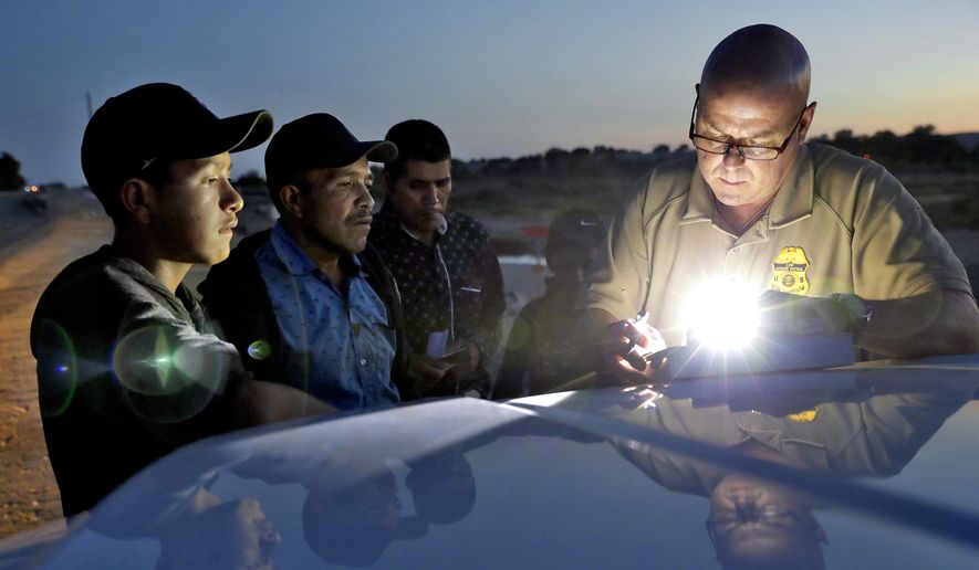 A U.S. Customs and Border Patrol agent gathers information on four Guatemalan nationals, including two men and a pair of 12 and 13-year-old boys, Wednesday, July 18, 2018, in Yuma, Ariz. Thousands of families and unaccompanied children are continuing to cross the U.S. border in Arizona and California even after learning of the government's family separation policy upon apprehension. (AP Photo/Matt York) ** FILE **