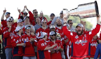 In this June 12, 2018, photo, Washington Capitals Alex Ovechkin, from Russia, right, holds up the Stanley Cup during a victory rally for the Washington Capitals in celebration of winning the Stanley Cup, on the National Mall in Washington. Ovechkin and the rest of the Washington Capitals will get to do something the franchise never has done: raise a banner signifying a Stanley Cup championship. (AP Photo/Jacquelyn Martin) **FiLE**