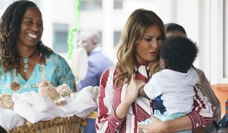 First lady Melania Trump holds a baby as she visits Greater Accra Regional Hospital in Accra, Ghana, Tuesday, Oct. 2, 2018. The first lady is visiting Africa on her first big solo international trip, aiming to make child well-being the focus of a five-day, four-country tour. (AP Photo/Carolyn Kaster)