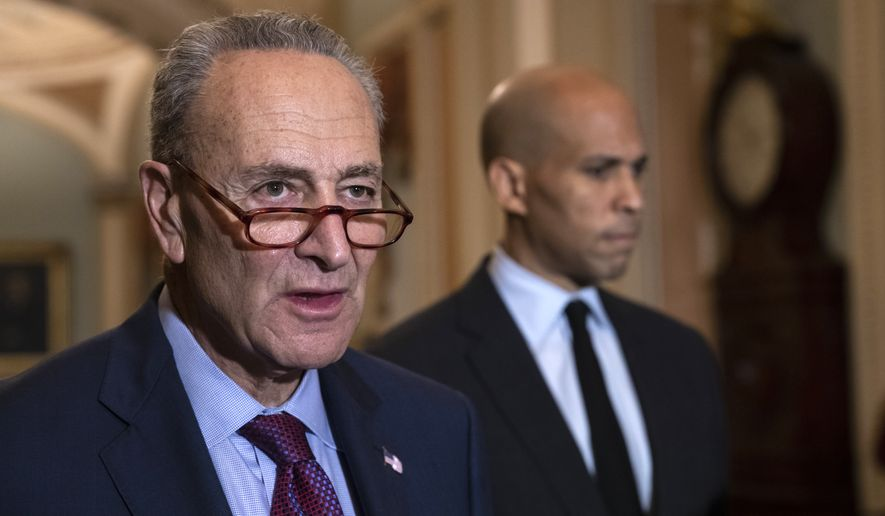 Senate Minority Leader Chuck Schumer, D-N.Y., with Sen. Cory Booker, D-N.J., at right, pauses as they speak to reporters about the political battle for confirmation of President Donald Trump's Supreme Court nominee, Brett Kavanaugh, following a closed-door Democratic policy meeting, at the Capitol in Washington, Tuesday, Oct. 2, 2018. (AP Photo/J. Scott Applewhite)