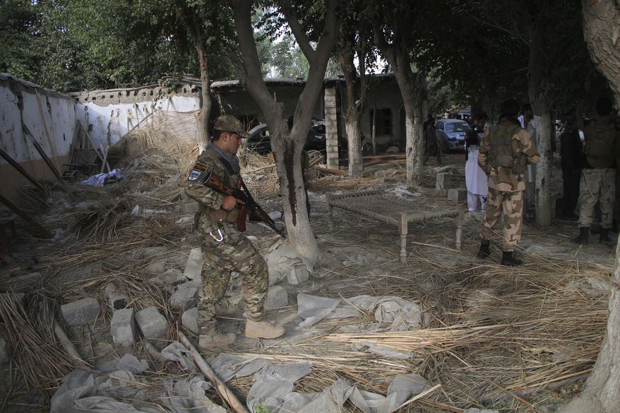 Afghan Security personnel inspect the site of a suicide attack in the Kama district of Nangarhar province, east of Kabul, Afghanistan, Tuesday, Oct. 2, 2018. The suicide bomber struck an election rally on Tuesday, killing at least 13 people and wounding more than 30, a provincial official said. (AP Photo)