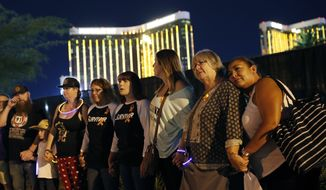 Survivors of a mass shooting form a human chain around the shuttered site of a country music festival on the first anniversary, Monday, Oct. 1, 2018, in Las Vegas. As people were linking arms and holding hands Monday night near the concert site, officials and several hundred others across town listened to bagpipes and the names of the 58 victims being read aloud. (AP Photo/John Locher)
