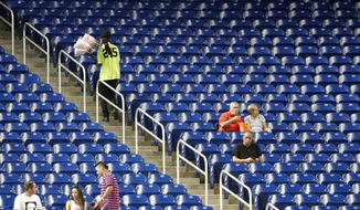 FILE - In this Sept. 17, 2018, file photo, a vender walks past empty seats during the third inning of a baseball game between the Miami Marlins and the Washington Nationals, in Miami. Major League Baseball's attendance dropped to its lowest level since 2003, and six stadiums set record lows. (AP Photo/Wilfredo Lee) ** FILE **