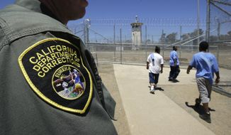 FILE - In this June 20, 2018 file photo , inmates pass a correctional officer as they leave an exercise yard at the California Medical Facility in Vacaville, Calif. In a final flurry of legislation before he leaves office in January, termed-out Gov. Jerry Brown signed a number of bills with his long-term goal of reducing mass incarceration, rehabilitating juvenile offenders, trimming lengthy prison sentences and offering second chances to the criminally convicted. (AP Photo/Rich Pedroncelli, file)