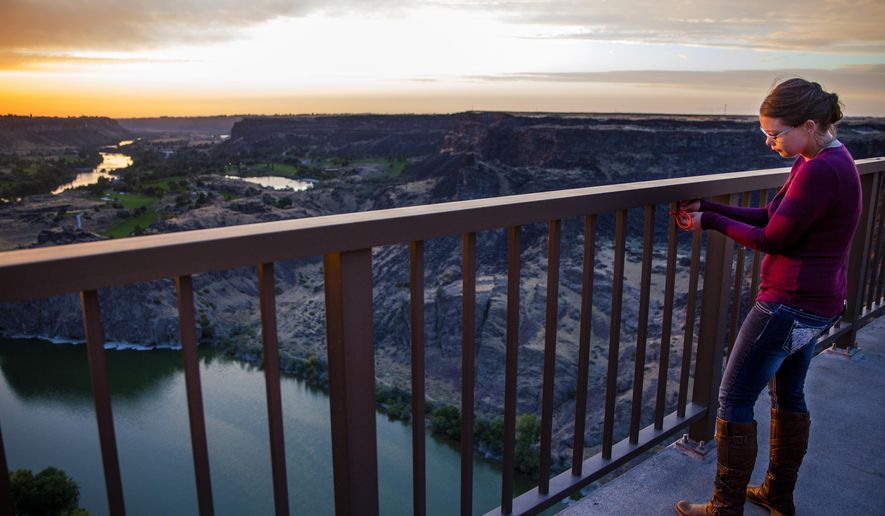 Lindsey Tadlock hangs a 'Love Yourself' bracelet from the I.B. Perrine Bridge on Thursday, Sept. 13, 2018, near the Twin Falls Visitor Center in Twin Falls. Tadlock lost her father to suicide when she was 14. (Pat Sutphin/The Times-News via AP)