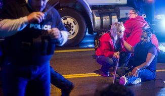 People gather to tend to a protester in the street after a truck collided with into protesters calling for the right to form unions Tuesday, Oct. 2, 2018, in Flint, Mich. Police said the collision appears to be an accident. (Jake May/The Flint Journal via AP)