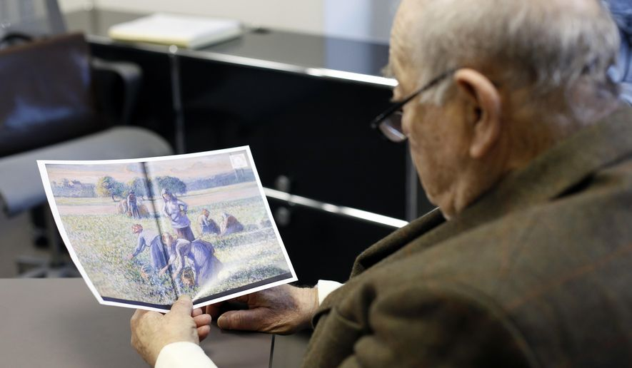 FILE - In this Tuesday, Nov. 7, 2017 file photo Jean-Jacques Bauer, looks at a reproduction of a valuable Pissarro painting he recovered, during an interview with the Associated Press, in Paris, France. A Paris appeals court has upheld a ruling ordering an American couple to return a Camille Pissarro painting to the descendants of a Jewish family that owned the art work when it was seized during World War II. (AP Photo/Thibault Camus, File)