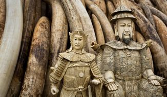 """FILE - In this Thursday, April 28, 2016 file photo, ivory statues stand in front of one of around a dozen pyres of elephant tusks, before being burned to encourage global efforts to help stop the poaching of elephants and rhinos, in Nairobi National Park, Kenya. American conservationist Esmond Martin researched the illegal ivory trade in Myanmar shortly before he was killed in Kenya in 2018 and now the research has been released in a report published Tuesday, Oct. 2, 2018 that says the illegal flow of ivory from Myanmar to neighboring China is continuing """"largely unabated."""" (AP Photo/Ben Curtis, File)"""