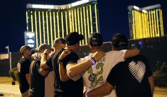 Survivors return to the scene of a mass shooting on the first anniversary, Monday, Oct. 1, 2018, in Las Vegas. Hundreds of survivors of the Las Vegas mass shooting have formed a human chain around the shuttered site of a country music festival where a gunman opened fire last year. (AP Photo/John Locher)