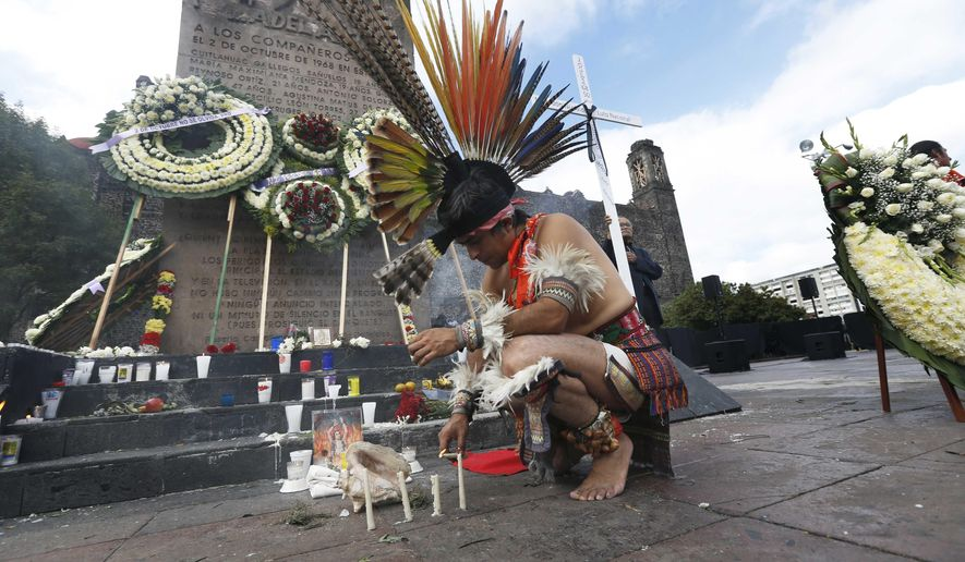 An Aztec dancer lights candles in Tlatelolco plaza where wreaths have been laid in commemoration of the 1968 massacre of student protesters by army troops 50 years ago, in Mexico City, Tuesday, Oct. 2, 2018. Students and surviving leaders of the 1968 student democracy movement are planning marches Tuesday to mark the anniversary of an event that caused such revulsion it helped spur long-term political reforms. (AP Photo/Marco Ugarte)