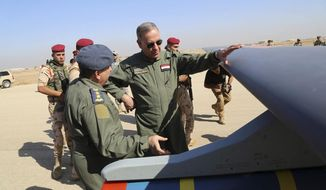 FILE - In this Oct. 10, 2015, file photo, Iraqi Defense Minister Khaled al-Obeidi, center, inspects a first Chinese drone to be used by the Iraqi Air Force before sending it to bomb Islamic State group positions at an airbase in Kut, 160 kilometers (100 miles) southeast of Baghdad, Iraq. Across the Middle East, countries locked out of purchasing U.S.-made drones due to rules over excessive civilian casualties are being wooed by Chinese arms dealers, who are world's main distributor of armed drones. The sales are helping expand Chinese influence across a region crucial to American security interests and bolstering Beijing's ambitions of being a world leader in high-tech arms sales. (AP Photo, File)