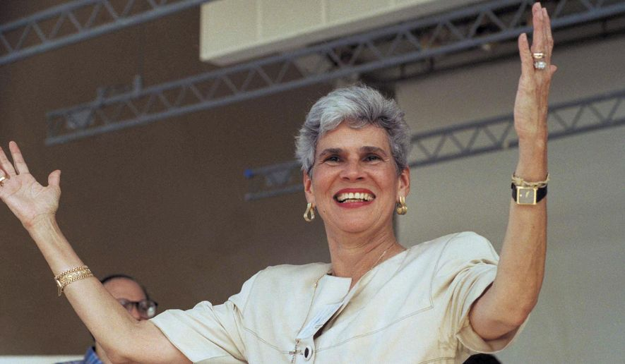 """FILE - In this Sept. 17, 1989 file photo, Nicaraguan presidential candidate Violeta Chamorro raises her arms as she receives a warm welcome from some 2,000 Nicaraguan exiles who turned out in Miami for a rally and independence day celebration. Chamorro's family put out a statement on Oct. 1, 2018 that the former president has been hospitalized in Managua, Nicaragua where she is in """"delicate condition"""" after a stroke. (AP Photo/Kathy Willens, File)"""