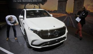 Media people look at a Mercedes-Benz EQC, electric luxury SUV during a media presentation on the eve of Paris Auto Show in Paris, France, Monday, Oct. 1, 2018. Doubts about diesel, Brexit, trade worries, tighter emissions controls. Those are the challenges that will be on the minds of auto executives when they gather this week ahead of the Paris Motor Show at the Porte de Versailles exhibition center. (AP Photo/Michel Euler)